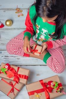 Het leuke donkerbruine meisje met haar stelt op kerstmisdag voor