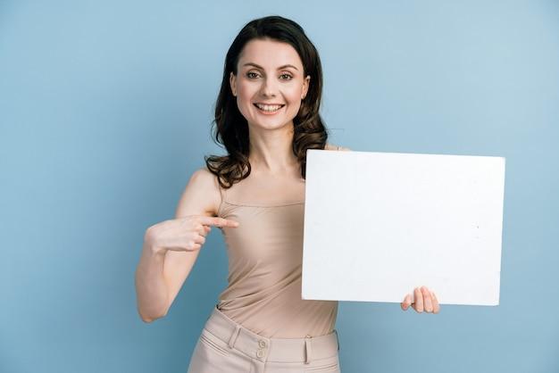 Het leuke, glimlachende meisje dat een wit vel papier vasthoudt, wijst er met haar vinger naar