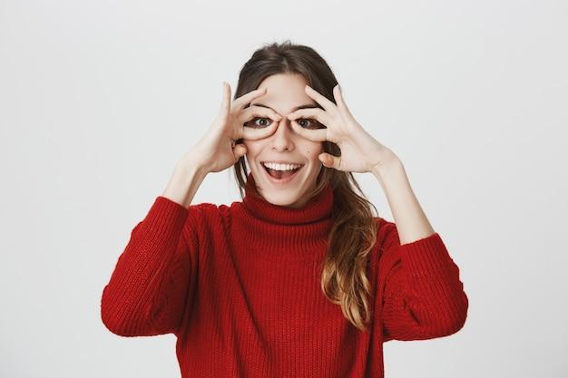 Het leuke grappige meisje glimlachen, maakt glazen van handen