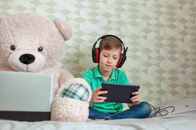 Het leuke jonge geitje die in hoofdtelefoons op digitale tablet naast een stuk speelgoed spelen draagt thuis kijkend in computer.