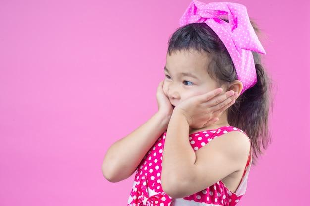 Het leuke jonge meisje dat een rood gestreept overhemd draagt, bond een roze boog op het hoofd en roze.