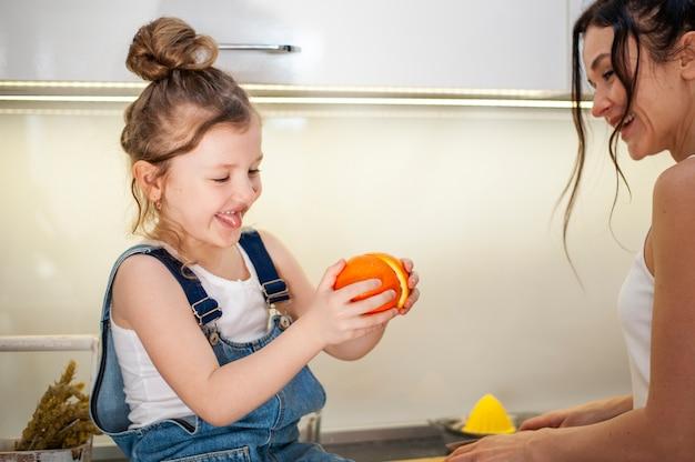 Het leuke jonge meisje en moeder spelen met vruchten