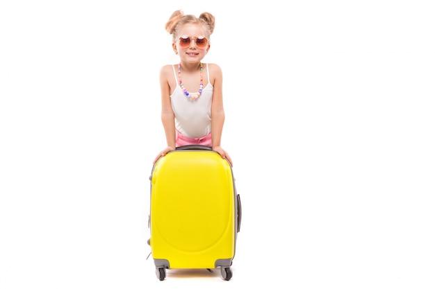 Het leuke jonge meisje in wit overhemd, roze borrels en zonnebril bevindt zich dichtbij gele koffer
