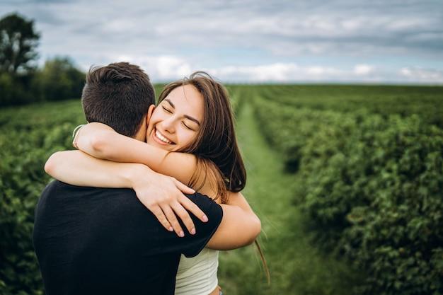 Het leuke jonge meisje met lang haar koestert haar minnaar, glimlachend en met haar ogen dicht. jong koppel wandelen in een veld in de natuur