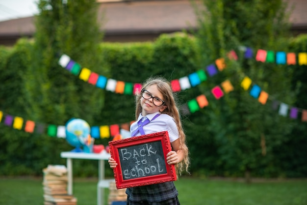 Het leuke jonge meisje stellen met kleine schoolraad tegen vlaggenachtergrond.