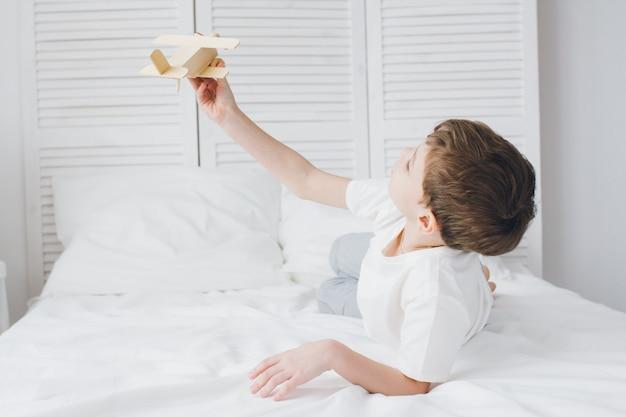 Het leuke jongen spelen met houten vliegtuigzitting op het bed