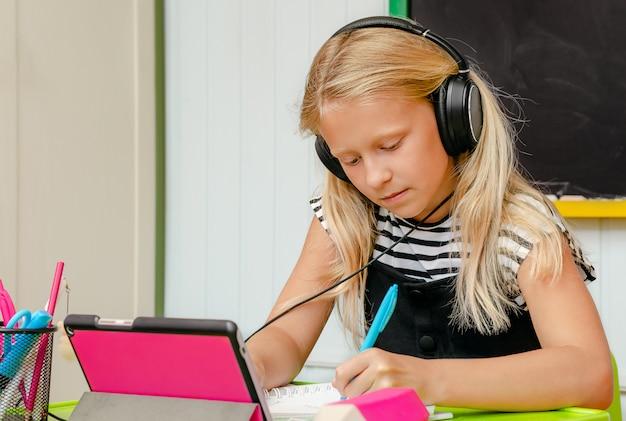 Het leuke kaukasische schoolmeisje is op thuisonderwijs. online onderwijs. kopieer ruimte