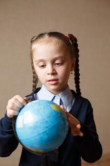 Het leuke kindmeisje kijkt de bol