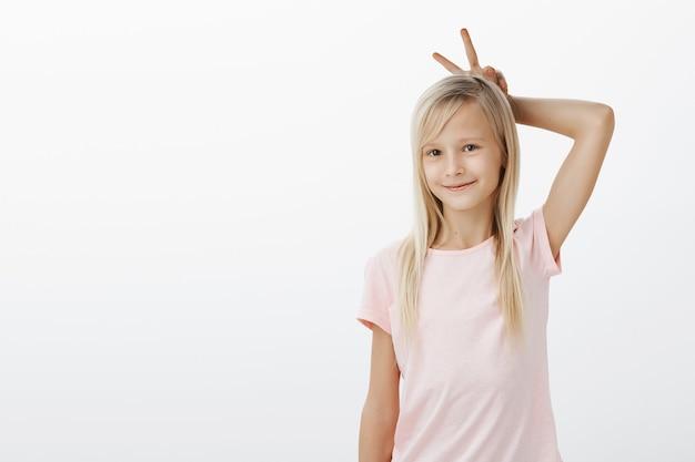 Het leuke kleine blonde meisje glimlacht en maakt konijnenoren met vingers achter hoofd