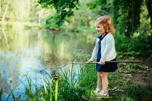 Het leuke kleine blondemeisje is tegen de achtergrond van water en g