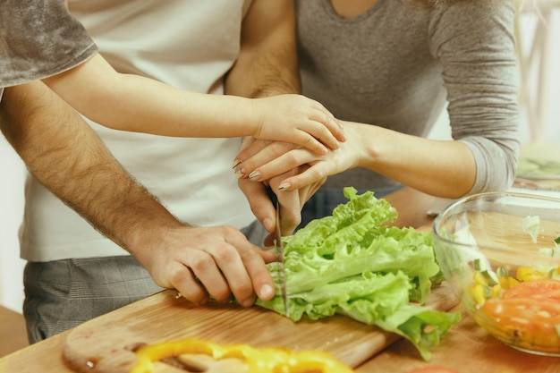 Het leuke kleine meisje en haar mooie ouders snijden groenten