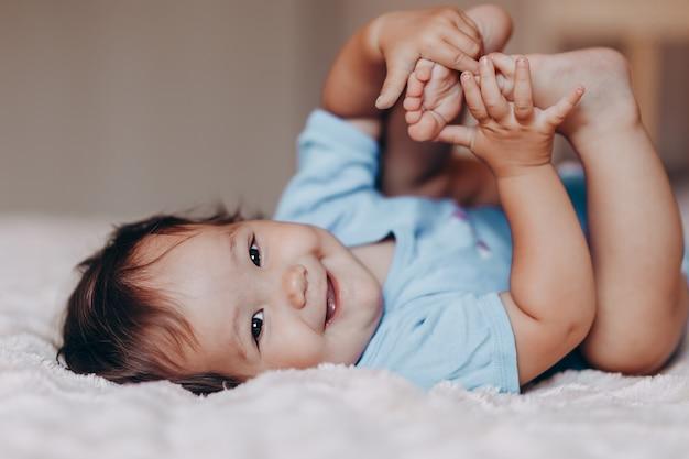 Het leuke lachende één éénjarigemeisje dat op bed ligt en camera bekijkt raakt haar voeten