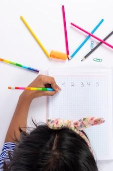 Het leuke linkshandige meisje schrijft met een potlood in haar notitieboekje.