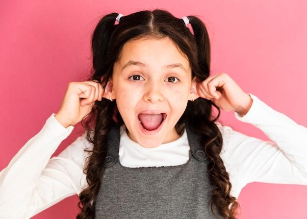 Het leuke meisje dat haar oren terugtrekt stelt