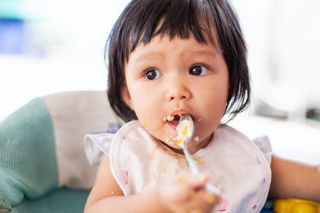 Het leuke meisje die van het baby aziatische kind alleen voedsel eten en een puinhoop maken