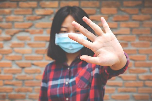 Het leuke meisje draagt masker en maakt eindehand van andere prople onb rick muurmuur