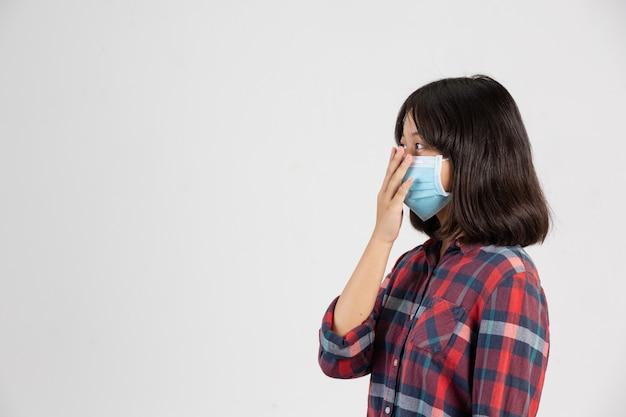 Het leuke meisje draagt masker en steekt met de hand haar hand op terwijl dichte mond op witte muur.