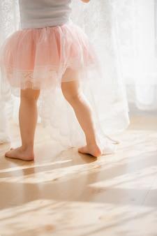 Het leuke meisje droomt ervan een ballerina te worden. kind in een roze tutu dansen in een kinderkamer