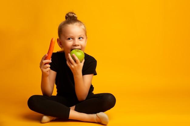 Het leuke meisje eet wortel en appelen, die over geel worden geïsoleerd. gezond eten