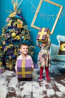 Het leuke meisje en de jongen glimlachen en houden giften onder de kerstboom. broer en zus pakken geschenkdozen uit op kerstavond.