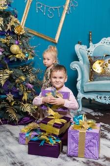 Het leuke meisje en de jongen glimlachen en houden giften onder de kerstboom