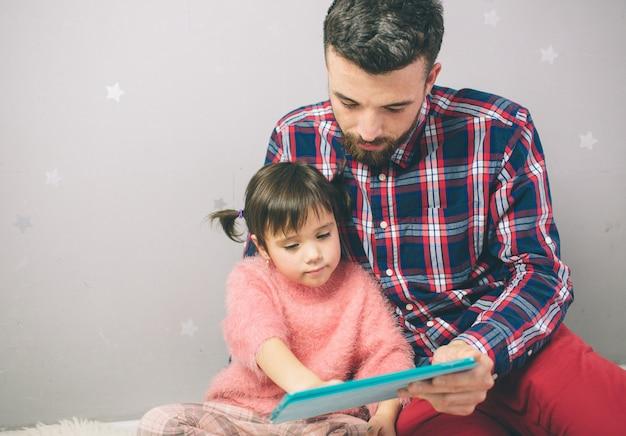 Het leuke meisje en haar knappe vader gebruiken een digitale tablet en glimlachen, thuis zittend.