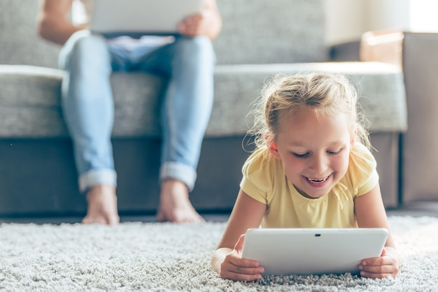 Het leuke meisje gebruikt een digitale tablet en het glimlachen.