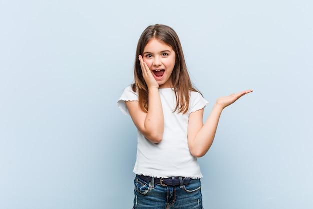 Het leuke meisje houdt exemplaarruimte op een palm, houdt wang overhandig verbaasd en opgetogen
