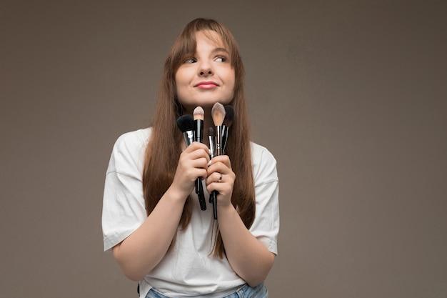 Het leuke meisje houdt make-upborstels dichtbij de kin op een donkere muur