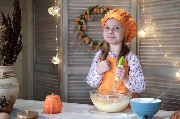 Het leuke meisje in een chef-kokkostuum kookt pompoentaart in de keuken. het proces van het maken van pompoentaart voor dankzegging
