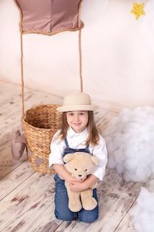 Het leuke meisje in een hoed koestert een teddybeer. kind speelt in een kinderkamer met een stuk speelgoed.