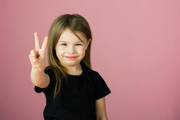 Het leuke meisje in een zwart mouwloos onderhemd en een rode rok op een roze pastelkleurachtergrond bekijkt de camera en glimlacht
