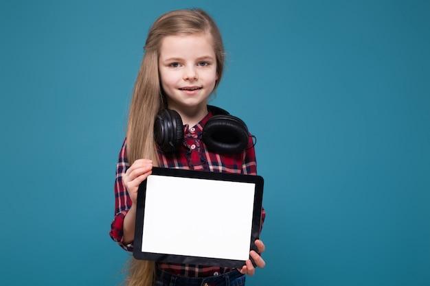 Het leuke meisje in overhemd en oortelefoons met lang haar houdt het stootkussen