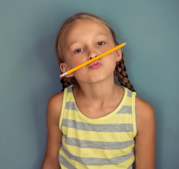 Het leuke meisje in vrijetijdskleding maakt gezichten met een potlood