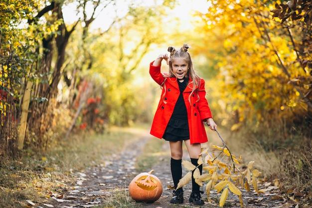 Het leuke meisje kleedde zich in openlucht in halloween-kostuum met pompoenen