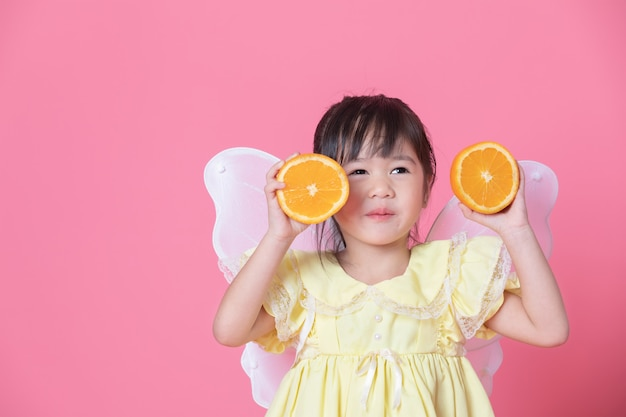 Het leuke meisje kleedt zich als een engel met witte vleugels die de helft van sinaasappel houden. gezond eten en levensstijlconcept. vegetarisch voedsel