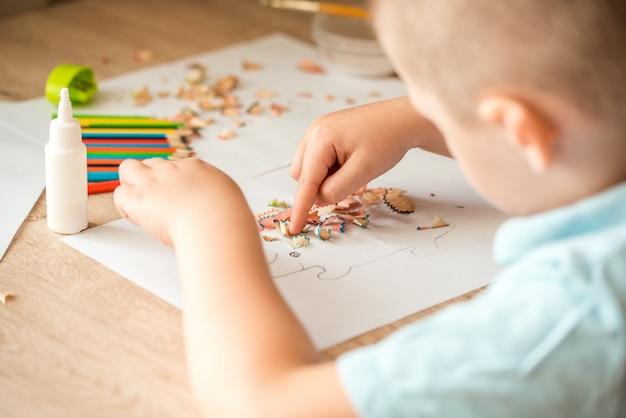 Het leuke meisje maakt applique lijmt kleurrijk huis, past kleurendocument toe gebruikend lijm terwijl het doen van kunsten en ambachten in kleuterschool of huis. idee voor de creativiteit van kinderen, een kunstproject gemaakt van papier.