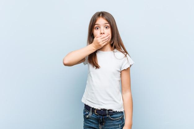 Het leuke meisje nadenkende kijken aan een exemplaarruimte die mond behandelen met hand.