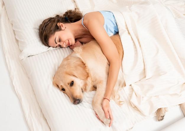 Het leuke meisje omhelst binnen haar eigen hondretriever in slaapkamer
