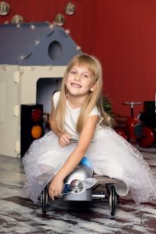 Het leuke meisje speelt met stuk speelgoed auto's, berijdt een stuk speelgoed schrijfmachinevliegtuig, gelukkige kinderjaren