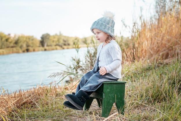 Het leuke meisje spelen door het water op mooie de herfstdag. herfstactiviteiten voor kinderen.