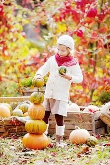 Het leuke meisje spelen met pompoenen in de herfstpark. herfstactiviteiten voor kinderen. schattig klein meisje bouwt een toren van pompoenen.