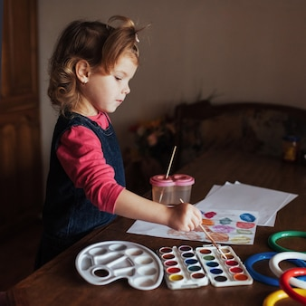Het leuke meisje trekt een cirkel van gekleurde verven
