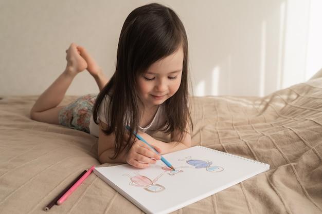 Het leuke meisje trekt een potloodtekening. een kind leert mensen tekenen. het kind ligt op bed en tekent met een blauw potlood