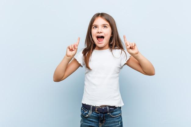 Het leuke meisje wijst op met beide voorvingers die omhoog een spatie tonen.