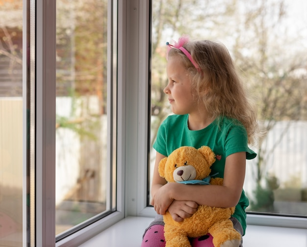 Het leuke meisje zit met haar teddybeer dichtbij het venster en kijkt buiten. peinzend kind