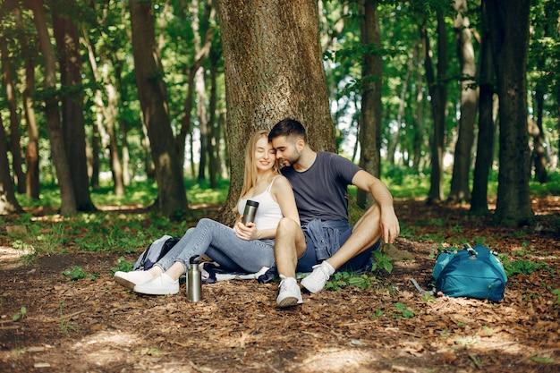 Het leuke paar heeft een rust in een de zomerbos