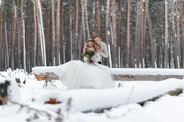 Het leuke paar in liefde met een boeket zit op de login achtergrond van het de winterbos. kunstwerk. winter bruiloft. kopieer ruimte