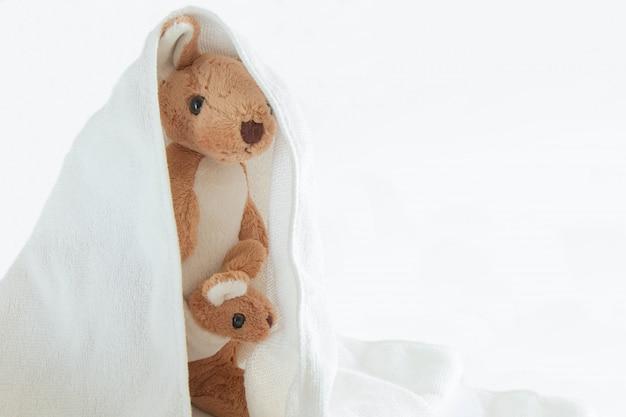 Het leuke paarmamma en de babykangoeroe spelen verstoppertje met een zak plastic, gelukkig gevoel concept.