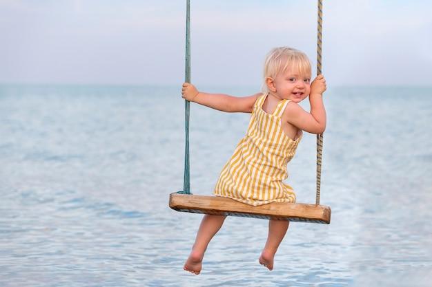 Het leuke peutermeisje zit op schommel tegen de overzeese achtergrond. levensstijl, portret van baby aan zee